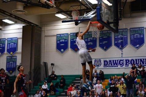 Senior Jomo Goings goes for a dunk during a game against Quince Orchard. The boys basketball team is looking for a long run in their season's playoffs.