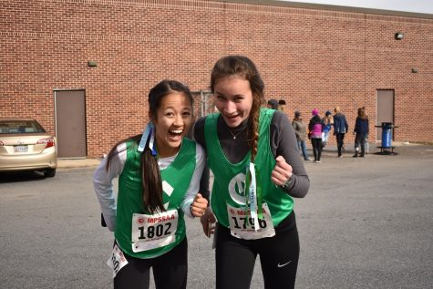 Lauren Kuo (left) and Jessica Bowen (right) get pumped up before their 2019 State Cross Country Meet.  Kuo and Bowen have been on the team since freshman year and were disappointed when their last season was cancelled.
