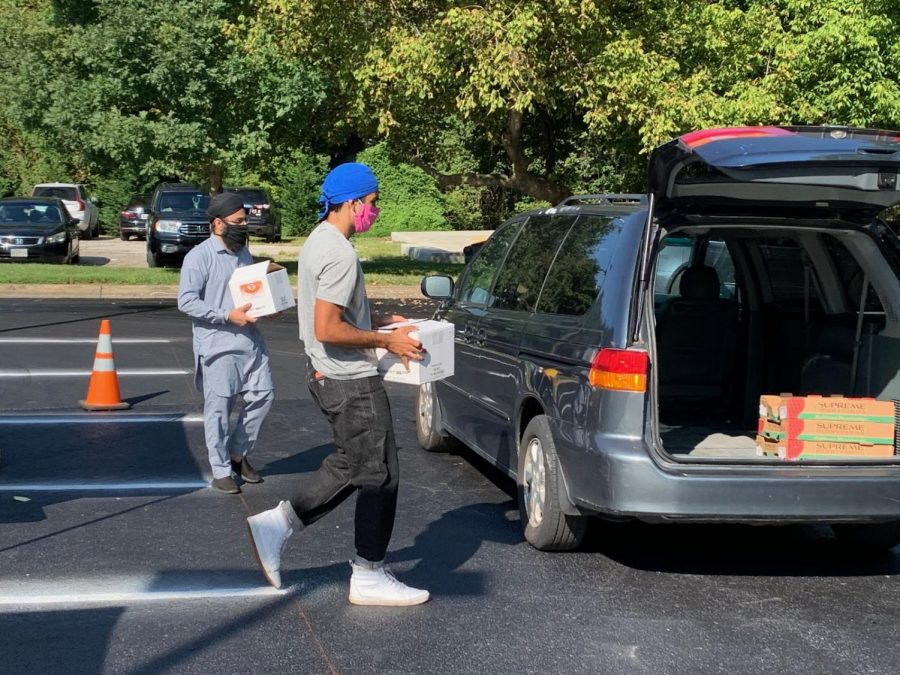 WCHS SGA president Jay Wood (front) and another GGSF volunteer help load cars with fresh produce, hot meals, and other food supplies for those dealing with food insecurity and other food needs.