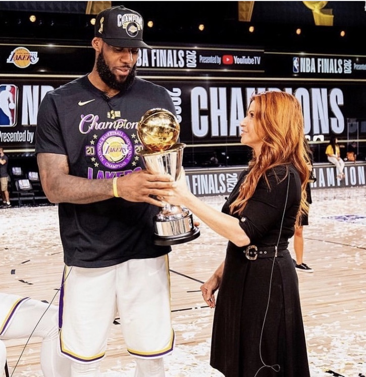 Los Angeles Lakers NBA finals MVP Lebron James stands next to reporter Rachel Nichols as the two hold his newly won NBA Finals Larry O'Brien Trophy. Nichols was the main sideline reporter covering the game in which Lebron won his fourth ever championship, and has built a strong relationship with players like Lebron over her many years reporting on the league.
