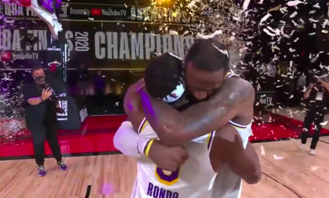 Confetti falling from the sky, LeBron James and Rajon Rondo are pictured hugging eachother and exchanging emotional words. Rondo and James won their first championship together as teammates on the Los Angeles Lakers.