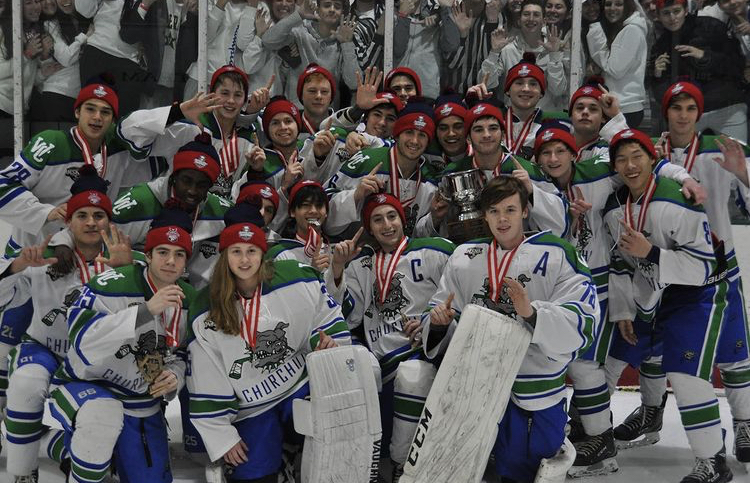After winning their sixth straight Maryland State Championship in 2020, the WCHS hockey team poses for a group photo on the ice right after the game. The players are wearing their championship medals and hats.