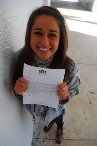 A senior stands smiling as she holds up her acceptance letter to University of Southern Florida. Although some feel overjoyed when they receive letters, these sentiments are not shared with all seniors.